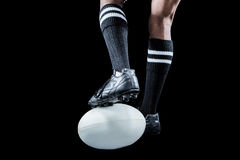 Sportsman keeping leg on ball while playing rugby. Against black background royalty free stock photos