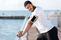 Sportsman listening to music fron blank screen smartphone on pier Royalty Free Stock Photos