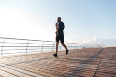 Sportsman listening to music and running on pier at sunset Royalty Free Stock Image