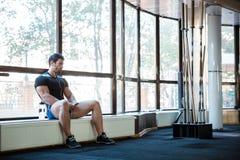 Sportsman listening to music sitting on windowcill Royalty Free Stock Image
