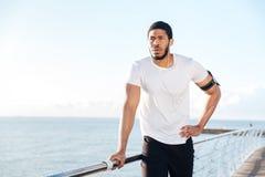 Sportsman listening to music using earphones standing on pier Stock Photos