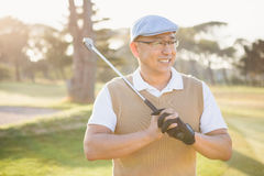 Sportsman looking away with his golf club. On a field stock photography