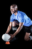 Sportsman looking away while keeping rugby ball on kicking tee Stock Photos