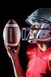 Sportsman looking up while holding American football Stock Image