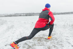 Sportsman making physical exercises in red protective nylon jacket. Sportsman is making physical exercises in red protective nylon jacket Royalty Free Stock Image