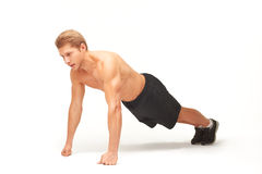 Sportsman making push-ups on fists in studio with straight arms. Muscular shirtless sportsman making push-ups on fists in studio with straight arms, looking Stock Photography