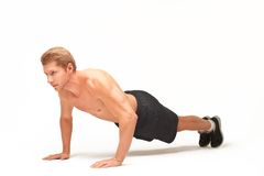 Sportsman making push-ups on palms in studio with bent arms. Muscular shirtless sportsman making push-ups on palms in studio with bent arms, looking straight Royalty Free Stock Image