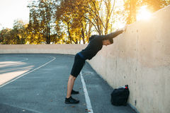 Sportsman making warming-up exercises. Male athlete training on open-air stadium, free space Stock Photos