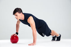 Sportsman man workout with fitness ball. Full length portrait of a sportsman man workout with fitness ball isolated on a white background Royalty Free Stock Photos