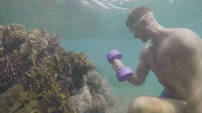 Sportsman in mask is making hand biceps exercises with dumbbells underwater. stock video footage