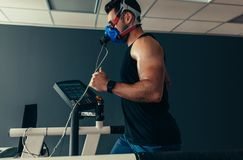 Athlete on treadmill at sports science lab. Sportsman with mask running on treadmill. Male athlete in sports science lab measuring his performance and oxygen stock photography