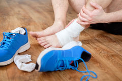 Sportsman massaging his injured ankle Royalty Free Stock Images