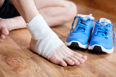 Sportsman massaging his injured ankle Royalty Free Stock Photos