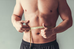 Sportsman. Measuring tape. Cropped image of attractive young sports man which measures his waist on gray background Stock Photography