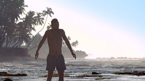 Sportsman meditates against ocean waves extreme slow. Muscular sportsman meditates against ocean waves and palms silhouettes in morning extreme slow motion stock video footage