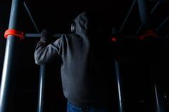 Sportsman at metal horizontal bar. Sportsman on training at metal horizontal bar in winter Stock Images