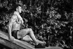 Sportsman with muscular body and towel sitting on concrete surfa Stock Photography