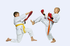 The sportsman with the orange belt beats kick on simulator in the hands of another athlete Stock Image