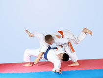 Sportsman with an orange belt threw athlete with a blue belt Royalty Free Stock Photo