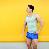 Sportsman over colorful yellow wall background. Fitness, sport concept, looks profile stock image