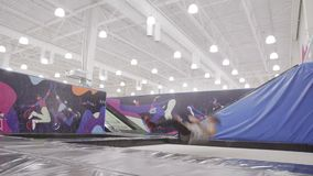 Sportsman is performing acrobatic elements on a trampoline stock footage