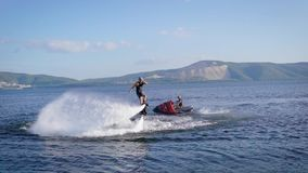 Sportsman is performing extreme tricks on flyboard on sea, controlling water flows by legs in summer day