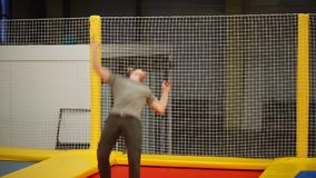 Sportsman is performing spinning and turning in air on a bouncer in sport hall stock footage