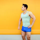 Sportsman posing over colorful yellow wall background. Fitness, sport concept, looking profile stock image