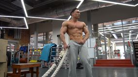 Sportsman pposing with heavy rope training at the gym.  stock video footage