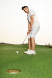 Sportsman putting golf ball into a hole. Sportsman putting a golf ball into a hole Royalty Free Stock Image