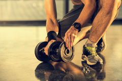 Sportsman putting weight on dumbbell in gym Stock Photos