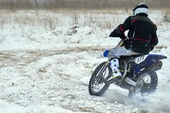 Sportsman racer man fulfills a fast ride on a motorcycle on the road extreme. The race track is very uneven. Cloudy winter day with a snowstorm stock photography