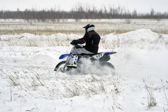 Sportsman racer man fulfills a fast ride on a motorcycle on the road extreme. The race track is very uneven. Cloudy winter day with a snowstorm royalty free stock images