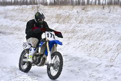 Sportsman racer man fulfills a fast ride on a motorcycle on the road extreme. The race track is very uneven. stock image