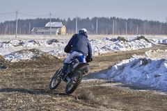 Sportsman racer man fulfills a fast ride on a motorcycle on the road extreme. The race track is very uneven stock photography
