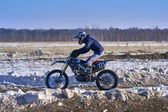 Sportsman racer man fulfills a fast ride on a motorcycle on the road extreme. The race track is very uneven. Sunny frosty winter day stock images