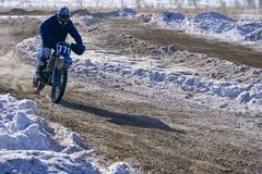 Sportsman racer man fulfills a fast ride on a motorcycle on the road extreme. The race track is very uneven. Sunny frosty winter d royalty free stock photo