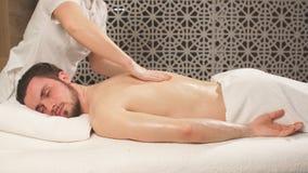 Sportsman is receiving back massage in Spa room.