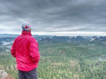 Sportsman in red with hands in pockets stand on the peak stock photography