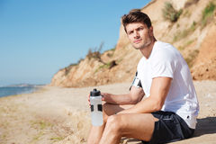Sportsman relaxing and drinking water on the beach Royalty Free Stock Photos