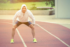 Sportsman resting on the running track outdoors stock photo