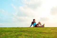 Sportsman resting after sport in the park and looking far away at the sunset Stock Photography
