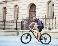 Sportsman riding bike next to old building royalty free stock photos