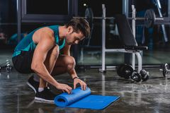 sportsman rolling up yoga mat royalty free stock photography