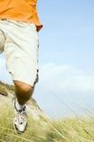 Sportsman running. A close crop of a sportsman running along a beautiful sandy beach wearing an orange t`shirt Stock Photo
