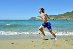 Sportsman running on the beach Royalty Free Stock Images