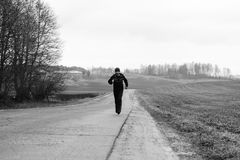 A sportsman is running on a highway in countryside Royalty Free Stock Image