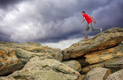 Sportsman running, jumping over rocks in mountain area. Royalty Free Stock Photos