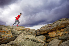 Sportsman running, jumping over rocks in mountain area. Stock Image