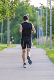 Sportsman running in park. Back view Royalty Free Stock Photography